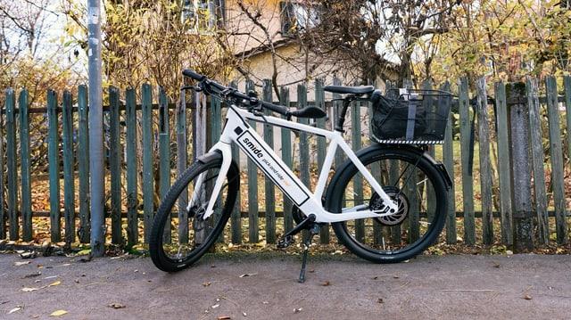 Weisses E-Bike an einem Gartenzaun.