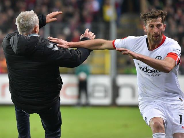 Freiburg-Captain David Abraham rammt Christian Streich.