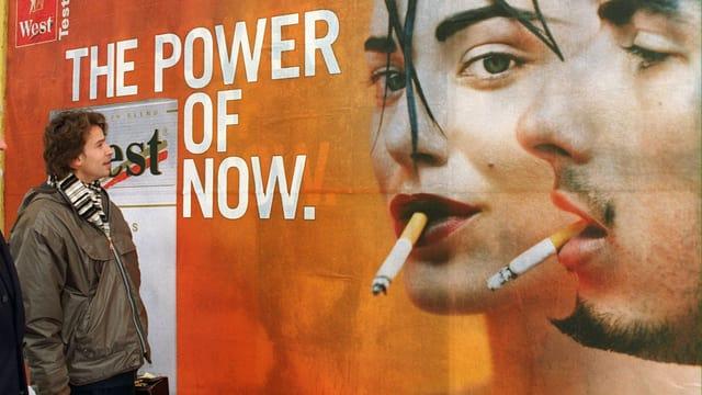Eine Person geht an einer Tabakwerbung vorbei.