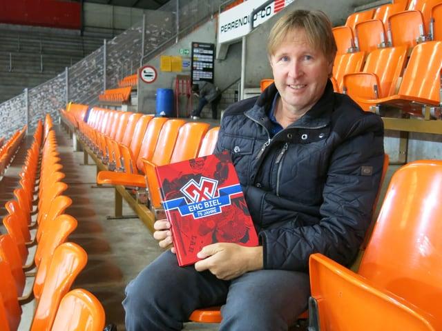 Beat Moning sitzt mit einem Buch im Eisstadion Biel