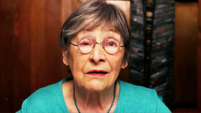ältere Frau mit Brille schaut in die Kamera