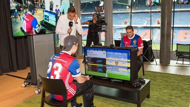 Zwei Männer in FCB-Dress sitzen je vor einem Computer und spielen ein digitales Fussballspiel