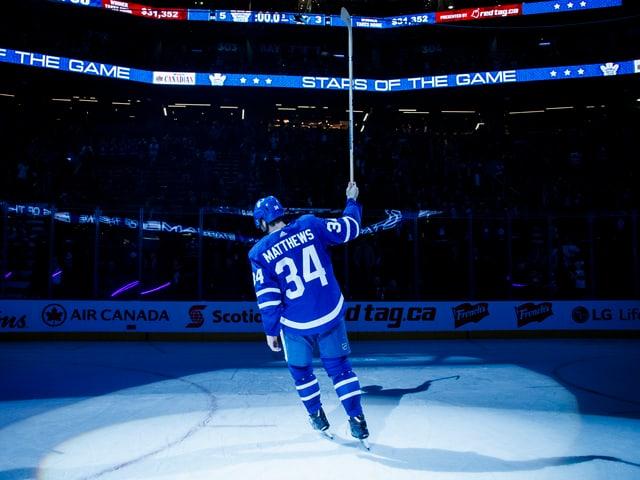 Auston Matthews dreht im Scheinwerferlicht eine Ehrenrunde auf dem Eis.