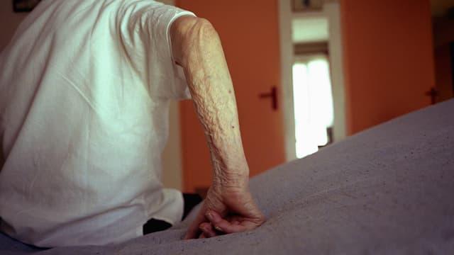 Eine ältere Person stützt sich mit dem Arm auf einem Pflegebett ab.