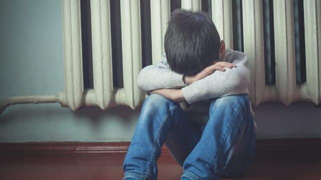 Ein Junge sitzt zusammengekauert am Boden.