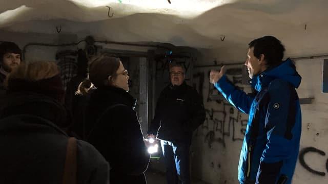 Mehrere Personen mit Taschenlampe in düsteren Räumen.