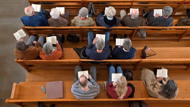 Menschen auf Kirchbänken, von oben fotografiert.
