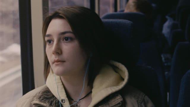 Frau schaut im Bus aus dem Fenster