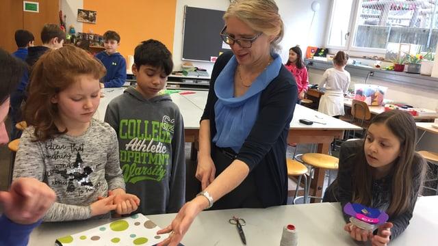 Eien Lehrerin in einem Schulzimmer zeigt drei Schülern, was sie machen sollen.