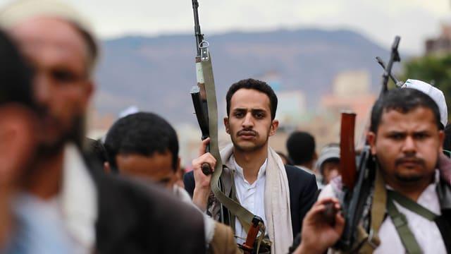 Huthi-Rebellen halten ihre Gewehre in die Luft.
