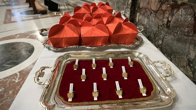 Rote Hüte und Ringe auf einem Tablett.
