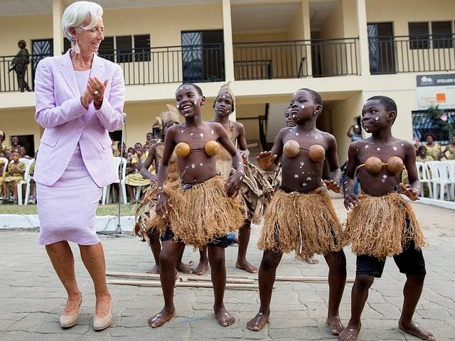 Christine Lagarde tanzt mit afrikanischen Kinder in traditioneller Tracht. (Kamerun, 2016)