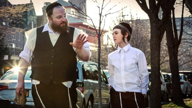 Ein Mann und ein Junge gehen nebeneinander eine Strasse entlang. Der Mann geht links, er trägt ein helles Hemd, eine dunkle Weste und eine Kippa. Er scheint dem Jungen etwas zu erklären und macht eine Geste mit der Hand. Der Junge geht rechts, trägt ein weisses Hemd, eine Kippa und Schläfenlocken.