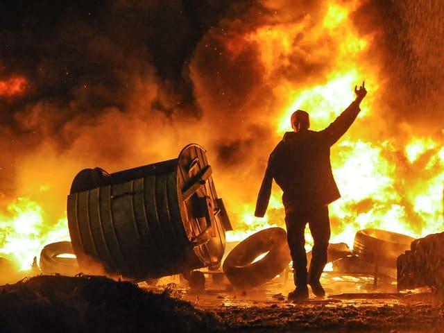 Demonstrant vor einer brennenden Barrikade, die Flammen schlagen meterhoch.