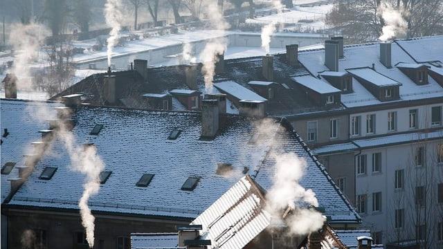 Schneebedeckte Dächer, qualmende Schornsteine (Bern).