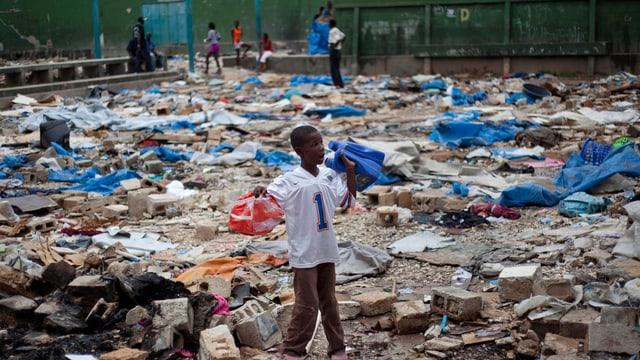 Ein Junge durchsucht den Platz eines ehemaligen Flüchtlingscamps nach Verwertbarem.