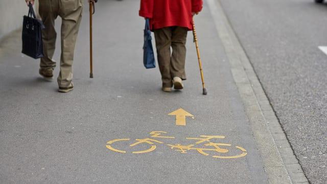 Zwei ältere Menschen, die auf dem Trottoir spazieren. Auf der Trottoir hat es ein Velo-Zeichen.