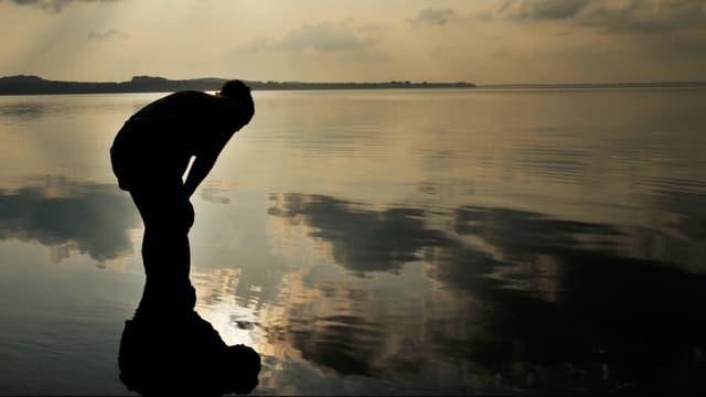Silhouette einer Frau, die auf das Wasser eines Sees blickt.