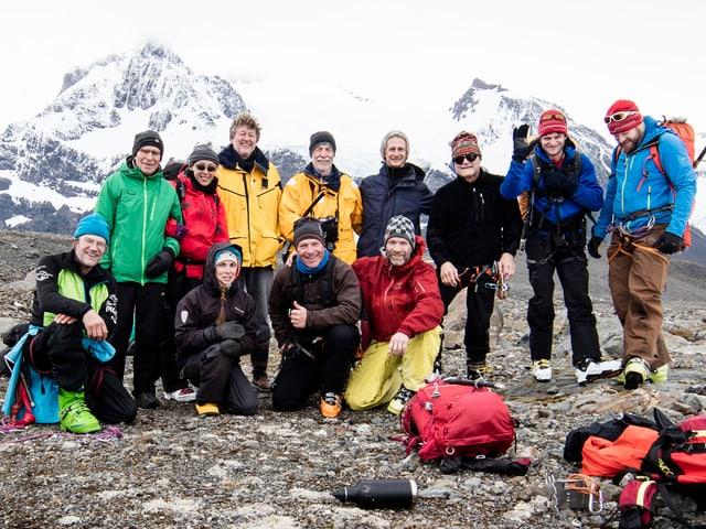 Die Gruppe posiert vor verschneiten Bergn.