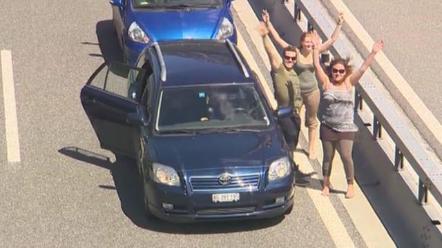 Leute winken auf der Autobahn neben ihrem stehenden Auto.