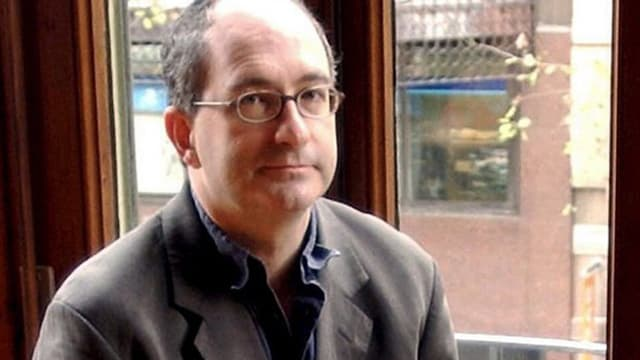 Der britische Autor John Lanchester sitzt in einem dunkelgrauen Anzug auf einem Fenstersims.