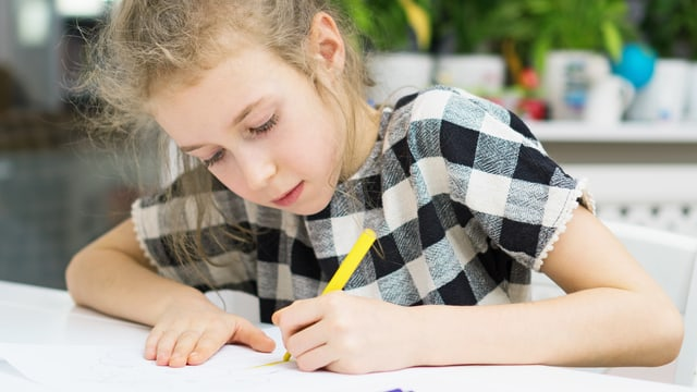 Ein Mädchen schreibt etwas mit der linken Hand.