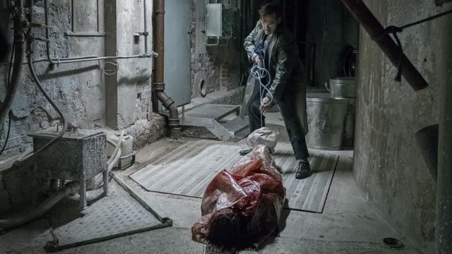 Ein mann zerrt eine blutige Leiche dem Boden entlang.