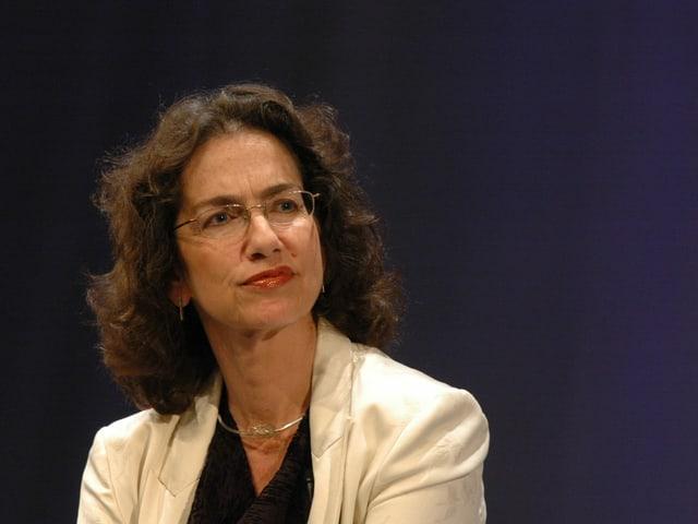 Eine Frau mit schulterlangen Braunen Haaren, Brille und hellem Blazer.