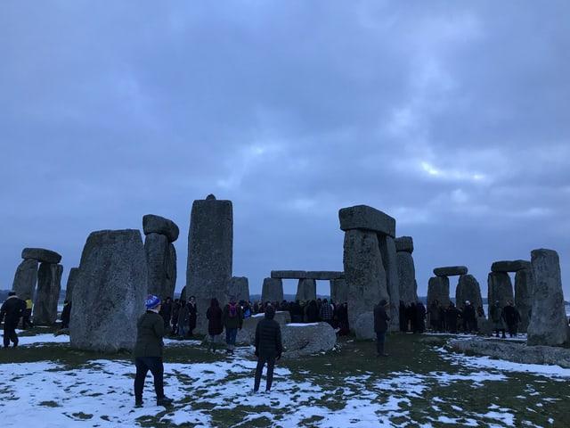 Touristen besichtigen Stonehenge.