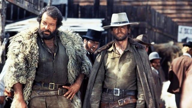 Zwei Männer stehen in einer Western-Stadt. Der eine trägt eine Felljacke, der anderen einen Cowboy-Hut.
