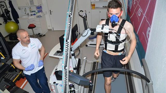 Physiotherapeut überprüft, wie ein Jungschiedsrichter auf dem Laufband rennt.