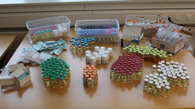 Fläschchen, Döschen, Spritzen und Tabletten in verschiedenen Farben stehen auf einem Tisch.