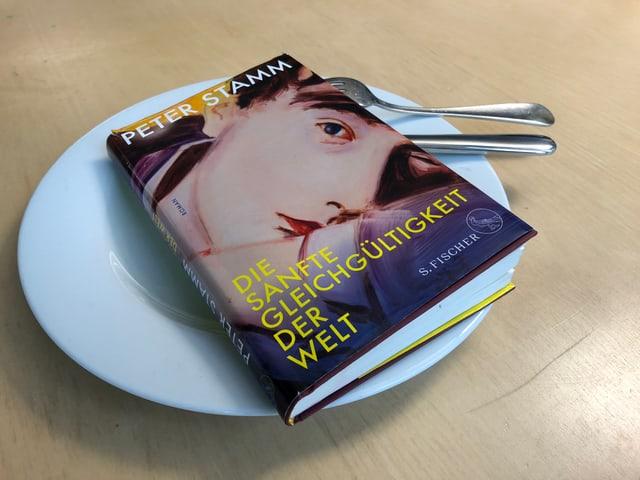 Das Buch «Die sanfte Gleichgültigkeit der Welt» von Peter Stamm liegt auf einem weissen Teller. Messer und Gabel sind hineingesteckt.