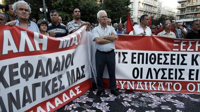 persunas che protestan cunter la povradad, dus placat cun scrittira greca
