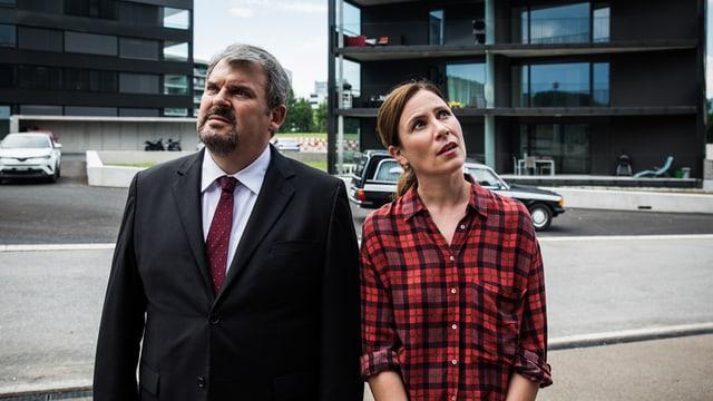 Mike Müller in Jacket und Barbara Terpoorten in kariertem Hemd vor Neubauten