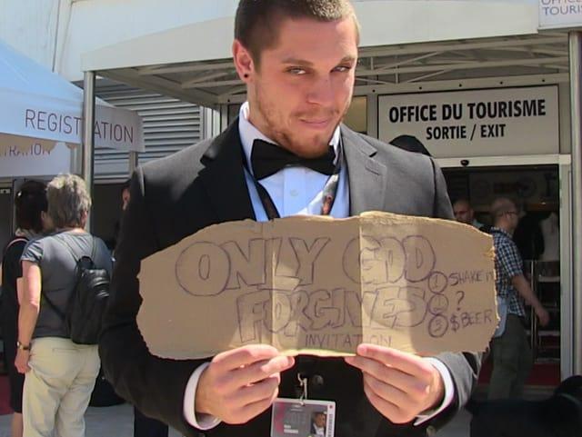 Ein junger Mann im Anzug steht da mit einem Schild in den Händen.