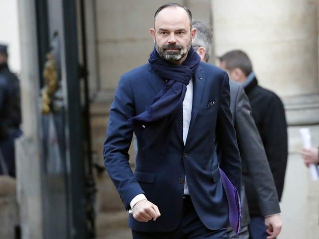 Premierminister Édouard Philippe läuft draussen.