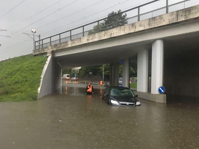 Auto steht im Wasser bei einer Unterführung.