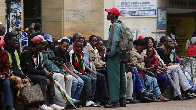 Menschen sitzn in einer Reihe auf einer Mauer.