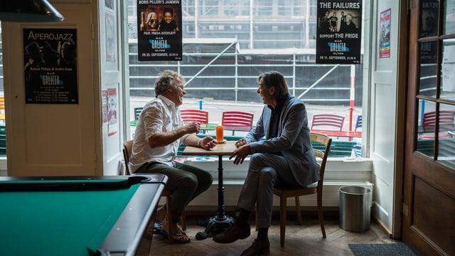 Alex Capus und Pedro Lenz diskutieren an eine Tisch in einer Bar, an der Wand hängen Plakate mit Konzerthinweisen