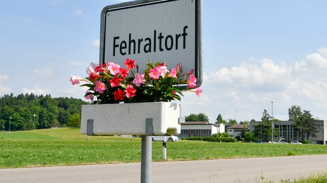 Eine Ortstafel am Dorfeingang von Fehraltdorf, darunter ein Blumenbeet.