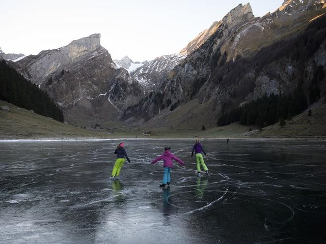 Drei Mädchen laufen auf dem spiegelglatt zugefrohrenen See Schlittschuh.