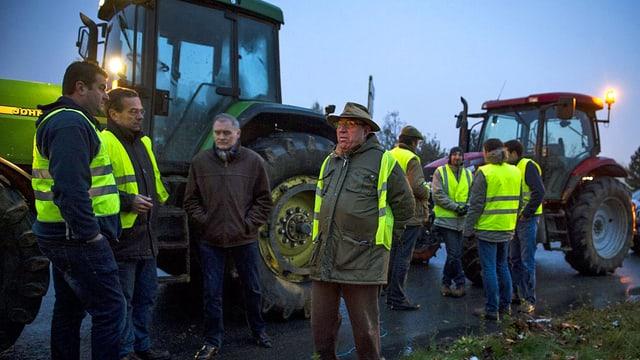 Bauern neben Traktoren.