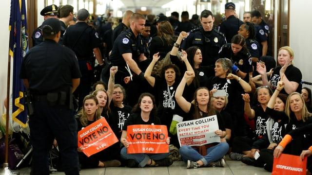 Frauen sitzen in einem Gang und rufen Slogans, sie halten Plakate in den Händen, darum herum stehen Polizisten.