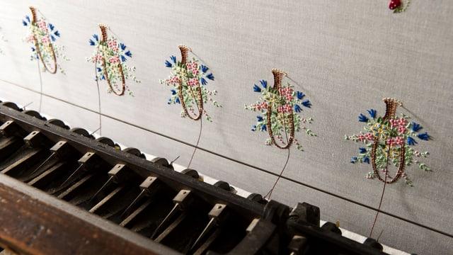 Eine klavierähnliche Tastatur, verbunden mit einer Stoffwand, die Stickereien trägt.