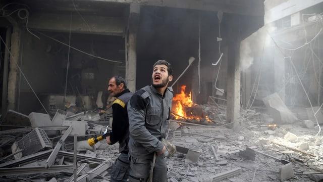 Zwei Helfer versuchen in zerbombten Häusern Feuer zu löschen.