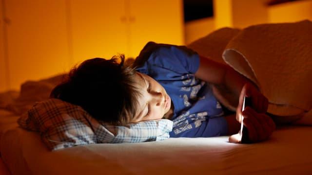 Ein Junge liegt im Bett und schaut auf sein Smartphone.