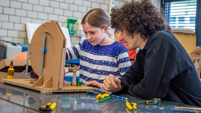 Mädchen werkelt unter Anleitung eines jüngeren Mannes an einem Bauteil aus Karton.