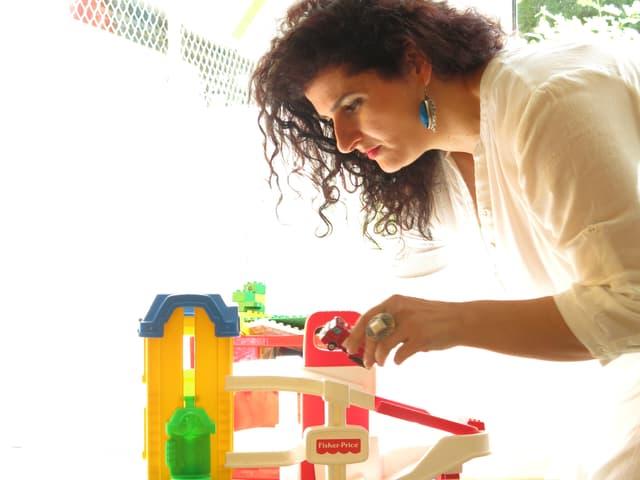 Suela Kasmi macht sich mit einem Spielzeugauto zu schaffen.