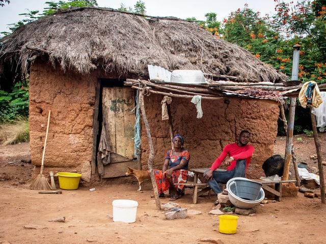 Einfache Lehmhütte, davor sitzen zwei Leute.